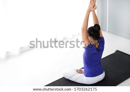 Healthy female practicing basic yoga at home. Beginner yoga woman  practice basic yoga pose during covid-19 home quarantine period.  Stretching & balance exercise at home on quarantine period concept.