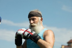 Healthy fighter bearded senior old man boxing gloves. Boxer with boxing glove.Handsome mature man practicing boxing kicks.
