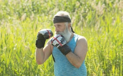 Healthy fighter bearded senior old man boxing gloves. Boxer with boxing glove. Handsome mature man practicing boxing kicks.