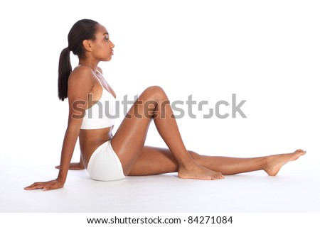 Healthy fit body of beautiful young black African American woman sitting on the floor, wearing white sports underwear and bare foot. Taken on white background.