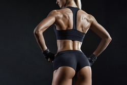 Healthy fit strong young woman in sportswear standing with her back looking over her shoulder. Fit young woman wearing sports gloves on black background. Fitness gym background. Girl sport.