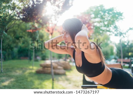 Healthy fit woman in sport clothes doing exercise on outdoors exercise machine
