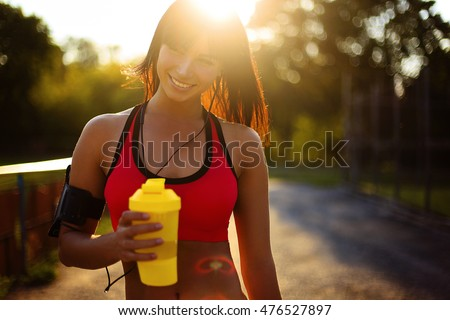 Shutterstock healthy fitness girl with protein shake. Smile sport woman in the sunny day