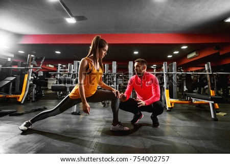 Healthy fitness shape young girl in sportswear doing legs stretching and exercising while talking with her personal trainer in the gym. Stock foto ©