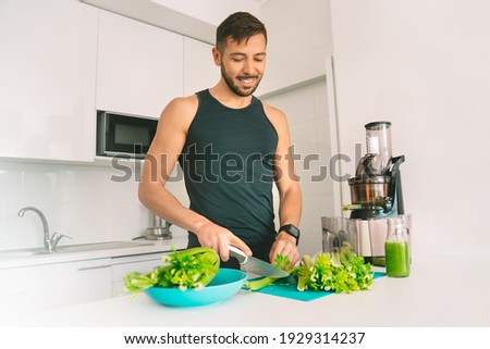 Healthy fitness sportsman making fresh detox homemade celery juice in juicer machine at home. Healthy food and lifestyle. Detox diet Photo stock ©