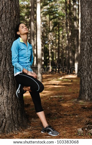 Healthy fitness woman resting in woods after a trail run. vitality relaxing athlete