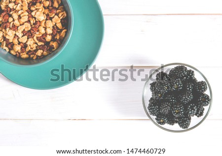 Healthy food: a healthy breakfast of cornflakes and blackberry berries on a white tree table