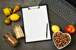 Healthy food and diet concept. Healthy products with laptop, clipboard and fruits,nuts on a gray concrete background. Flat lay.