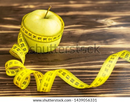 Healthy food and dieting concept. Green apple surrounded by measurement tape isolated on woody color table studio background with copy space. View from side top