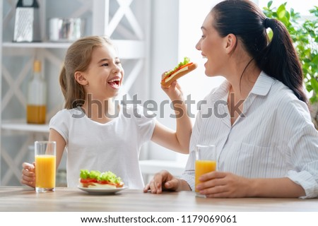 Healthy food at home. Happy family in the kitchen. Mother and child daughter are having breakfast. #1179069061