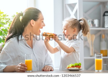 Healthy food at home. Happy family in the kitchen. Mother and child daughter are having breakfast.