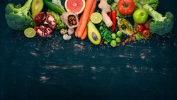 Healthy food background. Concept of Healthy Food, Fresh Vegetables, Nuts and Fruits. On a wooden background. Top view. Copy space.