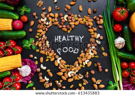 "Healthy food background. Healthy food concept with fresh vegetables for cooking  and some kind types of nuts. The phrase ""Healthy food"" is in the middle on the heart made from nuts. Dark background."