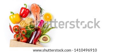 Healthy food background. Healthy food in paper bag fish, pasta, vegetables, fruits and wine on white background. Shopping food supermarket concept. Healthy eating, cooking dinner concept. Copy space