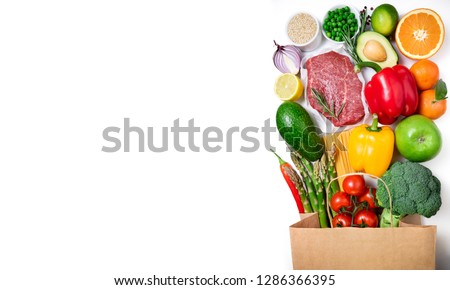 Healthy food background. Healthy food in paper bag meat beef, fruits, vegetables and pasta on white background. Shopping food supermarket concept. Long format with copy space