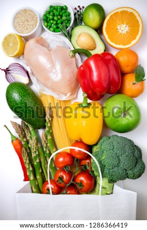 Healthy food background. Healthy food in paper bag meat, fruits, vegetables and pasta on white background. Shopping food supermarket concept. Top view #1286366419