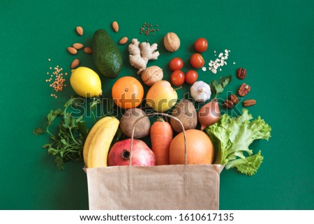 Healthy food background. Healthy vegan vegetarian food in paper bag vegetables and fruits on green, copy space. Shopping food supermarket and clean vegan eating concept.