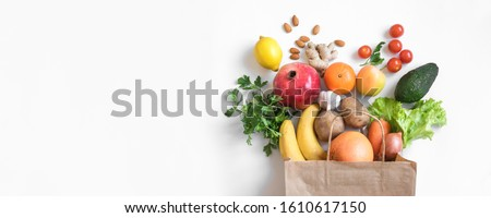 Healthy food background. Healthy vegan vegetarian food in paper bag vegetables and fruits on white, copy space, banner. Shopping food supermarket and clean vegan eating concept.