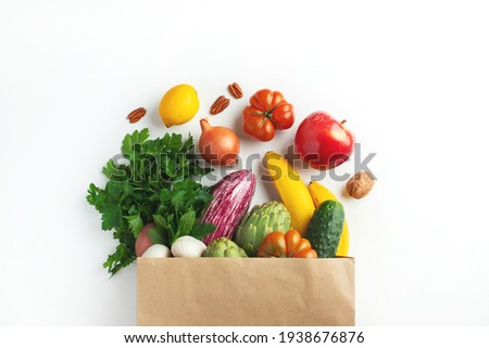 Healthy food background. Healthy vegan vegetarian food in paper bag vegetables and fruits on white, copy space. Shopping food supermarket and clean vegan eating concept.