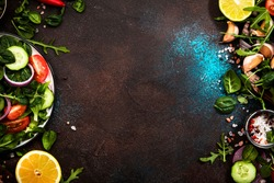Healthy food background. Ingredients for cooking salad. Cherry tomatoes, spinach, arugula, cucumbers, spices and oil with plate on brown background. Top view, copy space