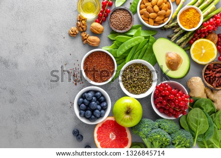 Healthy food background, spinach, quinoa, apple, blueberry, asparagus, turmeric, red currant, broccoli, mung bean, walnuts, grapefruit, ginger, avocado, almond, lemon, green peas and goji, top view #1326845714