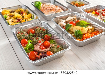 Healthy food background. Take away of natural organic meals in foil boxes. Fitness nutrition, meat, fresh salads, fruits and vegetables. Restaurant dishes delivery