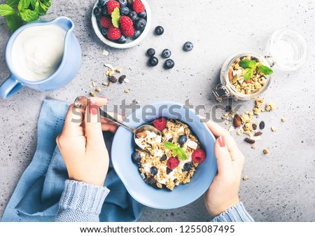 Healthy food background with homemade oatmeal granola or muesli with yogurt and fresh berries for healthy morning breakfast, top view, copy space. Women's hands