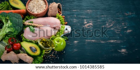 Healthy food. Chicken fillet, avocado, broccoli, fresh vegetables, nuts and fruits. On a wooden background. Top view. Copy space.