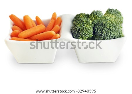 Healthy food choice from the vegetable garden: carrot and broccoli in cute white serving plate all on white background.