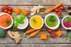 Healthy food, clean eating concept. Variety of colorful seasonal fall vegetables creamy soups with ingredients. Pumpkin, broccoli, carrot, beetroot, potato, tomato spinach. Flat lay