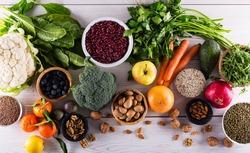 Healthy food clean eating : fruit, vegetable, seeds, superfood, cereals, leaf vegetable on black wood background with copy space, top view.