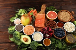 Healthy food clean eating selection: fish, fruit, vegetable, cereal, leaf vegetable on background