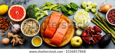 Healthy food clean eating selection: fish, fruit, vegetable, cereal, leaf vegetable on gray concrete background copy space