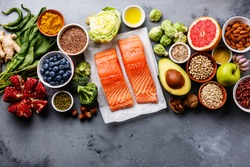 Healthy food clean eating selection: fish, fruit, vegetable, seeds, superfood, cereals, leaf vegetable on gray concrete background copy space