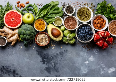 Healthy food clean eating selection: fruit, vegetable, seeds, superfood, cereals, leaf vegetable on gray concrete background copy space