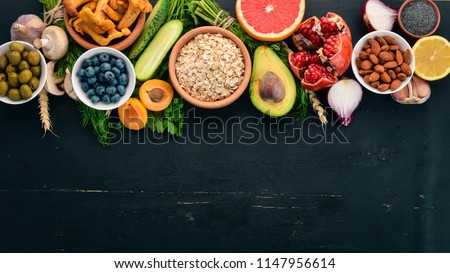 Healthy food clean eating selection: Vegetables, fruits, nuts, berries and mushrooms, parsley, spices. On a black background. Free space for text. #1147956614