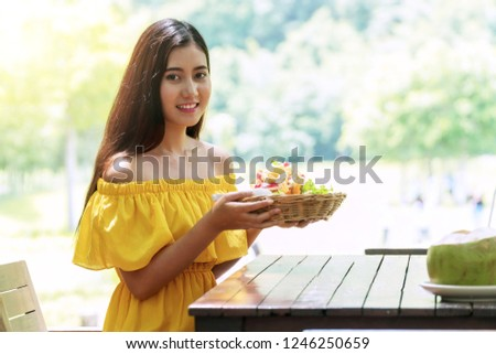 Healthy food concept. Cheerful smile young woman holding basket organic salad eating diet for health at garden restaurant on nature background.