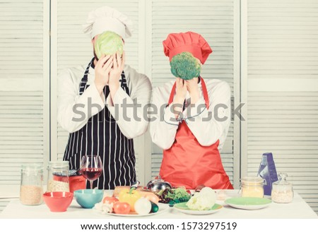 Healthy food concept. Couple cooking healthy vegetarian meal. Vegetarian family. Vegetarian nutrition and vegetable diet. Diet on their mind. Couple cooks hold cabbage and broccoli in front of face.