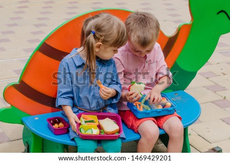 Healthy food concept. Girl and boy preschool students eating their lunches of sandwich, fresh vegetables and berries from lunch boxes sitting outdoor.