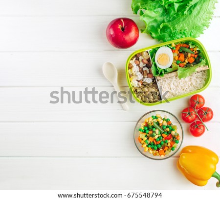 Healthy food concept: Lunch box filled with rice and mixed vegetables, boiled egg and snacks on white wooden background with copy space; top view, flat lay