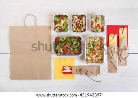 Healthy food delivery. Take away of natural organic low carb. Eat right concept, healthy food, fitness nutrition take away in aluminium boxes, cutlery and package, top view, flat lay at white wood #431943397