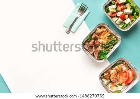Healthy food delivery. Take away of organic daily meal on blue, copy space. Clean eating concept, healthy food, fitness nutrition take away in foil boxes, top view. Сток-фото ©