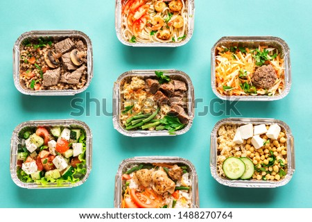 Healthy food delivery. Take away of organic daily meal on blue, copy space. Clean eating concept, healthy food, fitness nutrition take away in foil boxes, top view.