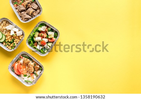 Healthy food delivery. Take away of organic daily meal on yellow, copy space. Clean eating concept, healthy food, fitness nutrition take away in foil boxes, top view.