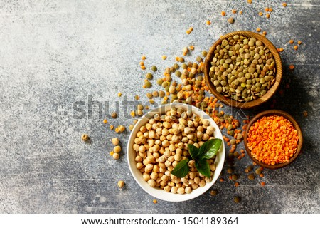 Healthy food, dieting, concept vegan protein source. Raw of legumes (chickpeas, red lentils, canadian lentils). Top view flat lay. Free space for your text.