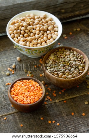 Healthy food, dieting, nutrition concept, vegan protein source. Raw legumes - red lentils and canadian lentils on wooden table.