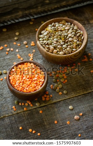 Healthy food, dieting, nutrition concept, vegan protein source. Raw legumes - red lentils and canadian lentils on wooden table. Copy space.