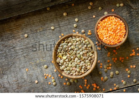 Healthy food, dieting, nutrition concept, vegan protein source. Raw legumes - red lentils and canadian lentils on wooden table. Top view on a flat background. Copy space.