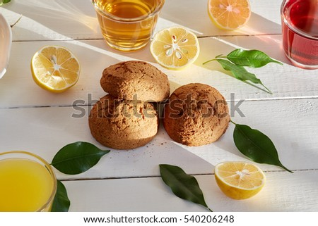 Healthy food & drink & natural diet food: Healthy breakfast. Fruits Juices Citrus fruits & bakery. Apple orange grapes & cherry juices lemon biscuit cake cookie. Top view White wooden table.