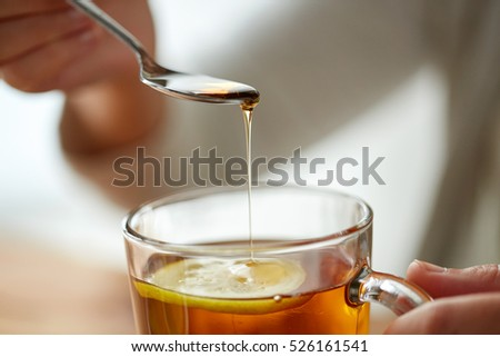 healthy food, eating and ethnoscience concept - close up of woman adding honey to tea cup with lemon #526161541